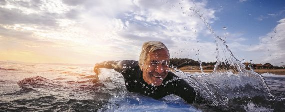 Active and happy senior man living to the fullest, surfing on a surfboard during his summer vacation