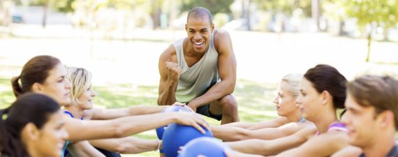 Personal Trainer Motivating People Exercising With Medicine Balls In Park