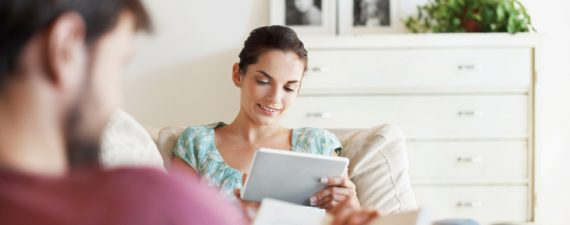 An attractive young woman using her tablet while her husband reads a book