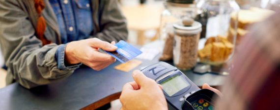 Shot of a customer paying for their order with a debit machine in a cafe