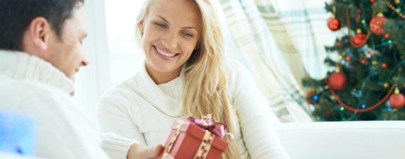 Young man giving his girlfriend Christmas present