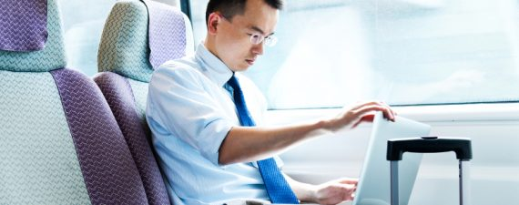 Asian businessman on train with laptop computer.