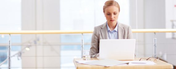 Female CEO typing on computer in empty office