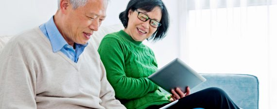 Happy senior asian couple sitting on sofa and  reading on a digital tablet at home.