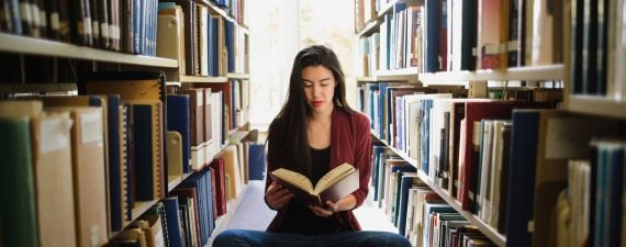 Young asian woman reading in library
