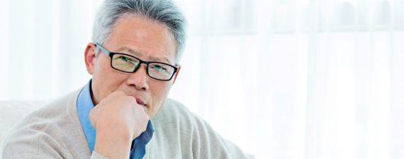 Asian senior man sitting at home and contemplating