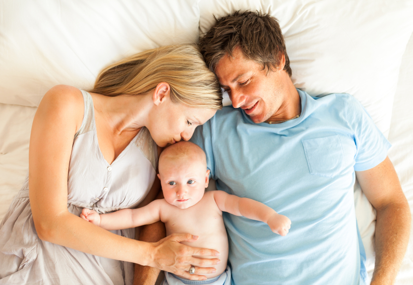Caring parents with baby lying in bed. Horizontal Shot.