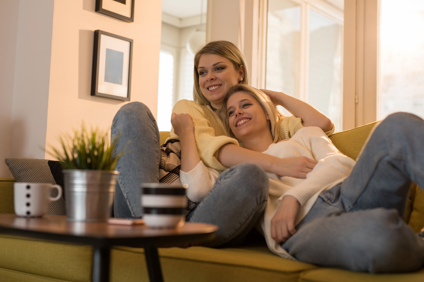 Young smiling female couple enjoying in their time at home.