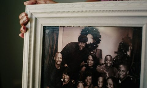 Taunya Kennedy holds a family portrait in her home in a suburb south of Chicago. Credit: Alyssa Schukar