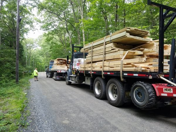 Flatbeds deliver the ingredients for Buck's two-story house. (Photo courtesy of Jennifer Buck.)