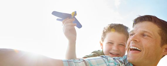 A cute little boy playing with an airplane while being carried on his father's back