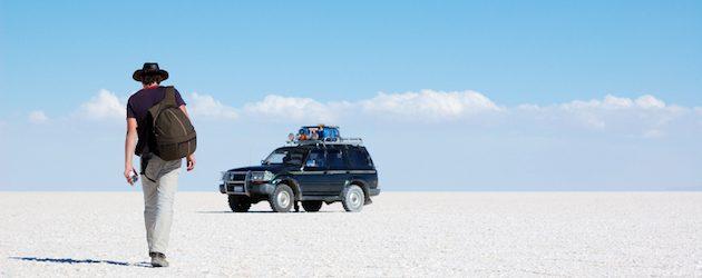 Backpacker walking to the car in salt desert, Bolivia