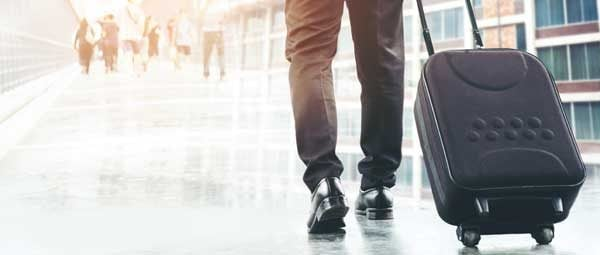 Business traveler carrying suitcase down a terminal