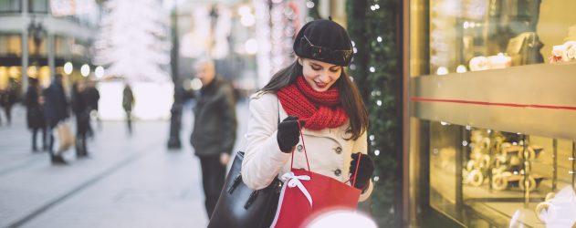 Young woman wearing a red scarf holds a red gift bag in front of a store window