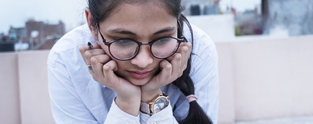 A female student, wearing round black-frame glasses and a white shirt, rests her chin in her hands