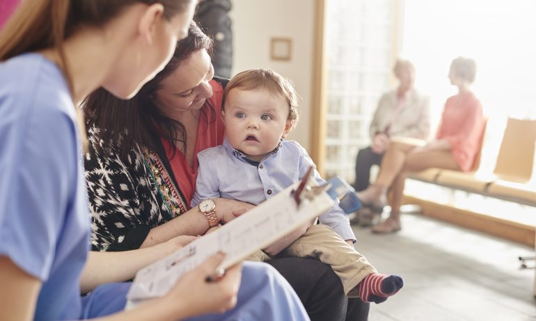 Mom holds a baby boy as they talk with a nurse at a doctor's office
