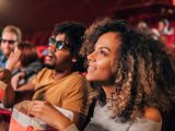 Smiling young couple looking up at screen in movie theater
