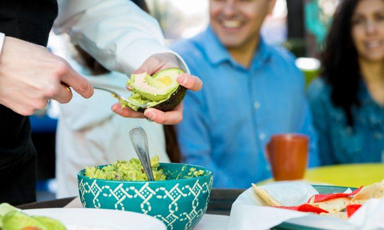 Restaurant server making table-side guacamole