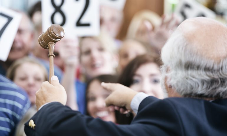 An auctioneer with a gavel points to bidders