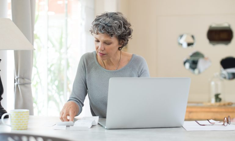 Senior woman at home working on bills with laptop
