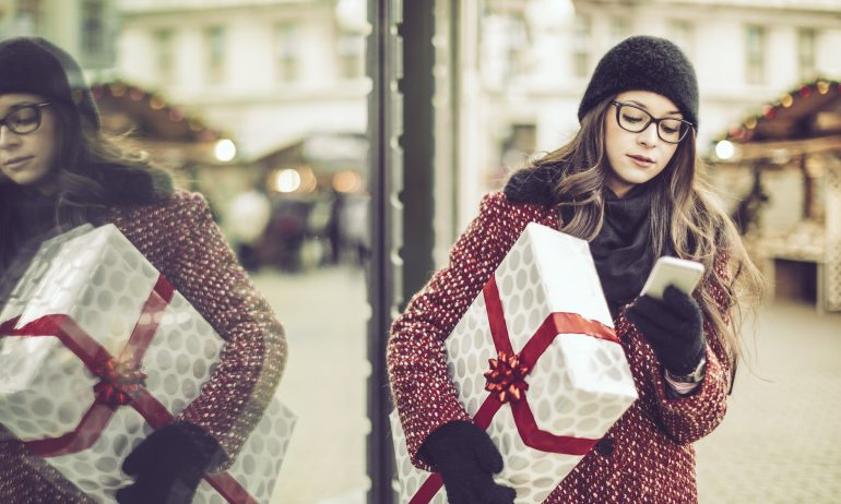 A young woman wearing a dark winter hat and glasses looks at her phone as she carries a Christmas package on a city street.