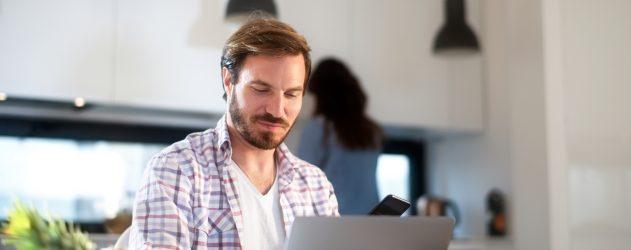 Man looking at laptop computer at kitchen table