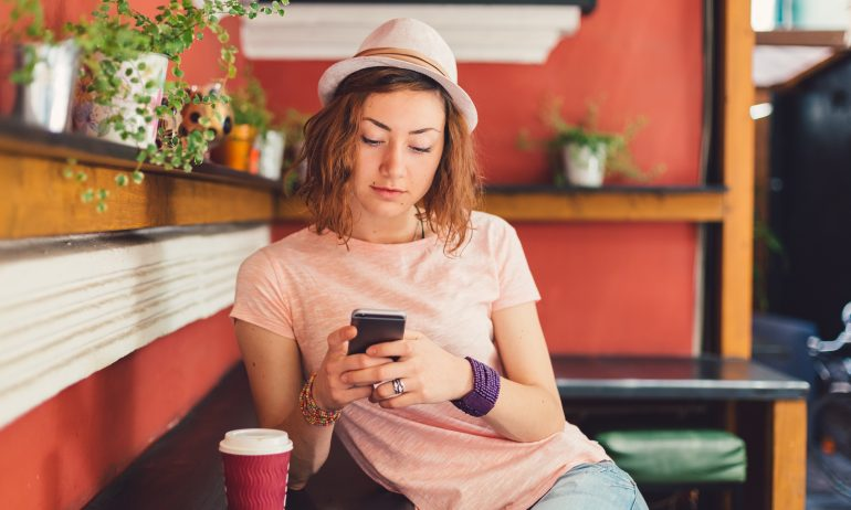 Young woman using cell phone in coffee shop