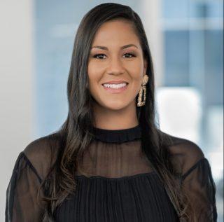 Rianka R. Dorsainvil blickt vor die Kamera und lächelt vor einem unscharfen Hintergrund.
