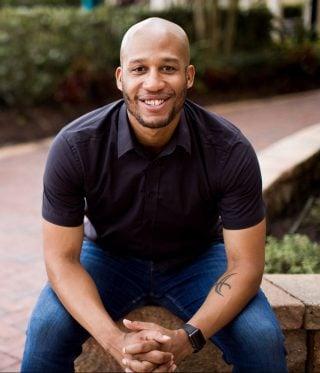 Rich Jones sitzt mit gefalteten Händen und Unterarmen auf den Knien auf einer Steinmauer und lächelt in die Kamera.