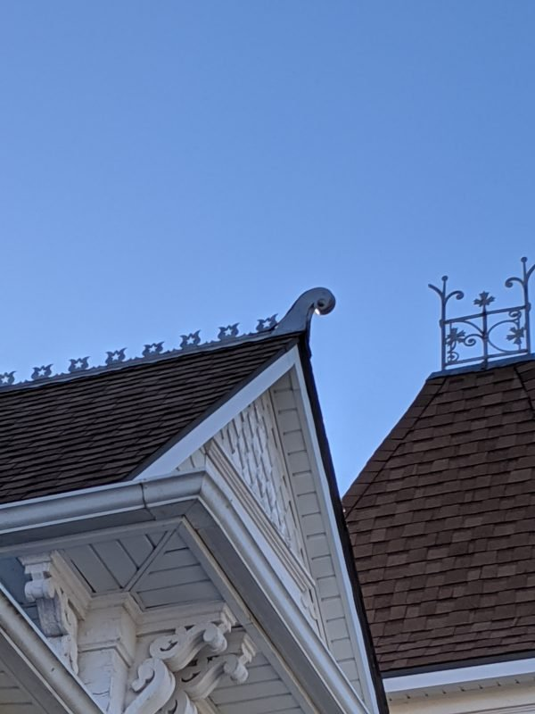Cut-out, rounded shapes line the top of the gable roof.