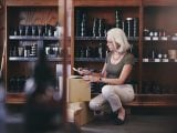 Senior saleswoman holding paper while crouching by boxes in deli