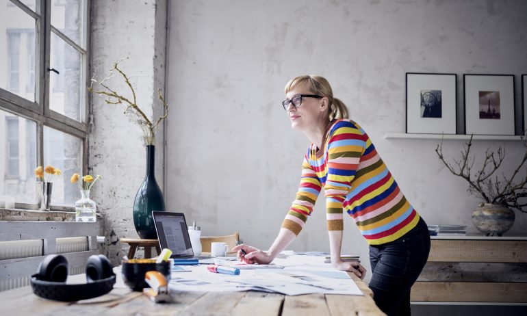 Portrait of smiling woman standing at desk in a loft looking through window