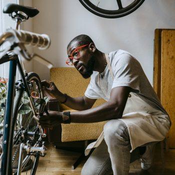 Shop owner repairing bicycle.