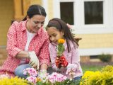 mother and daughter planting flowers in yard
