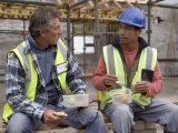 Two construction workers sitting down on a residential building site while eating their lunch.