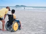 Rear View Of Man By Disabled Boy On Wheelchair At Beach
