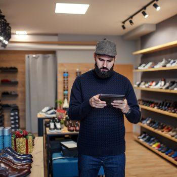 Male Owner Of Online Shoe Business Using Digital Tablet