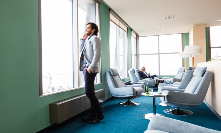 Businessman looking through window at airport lounge