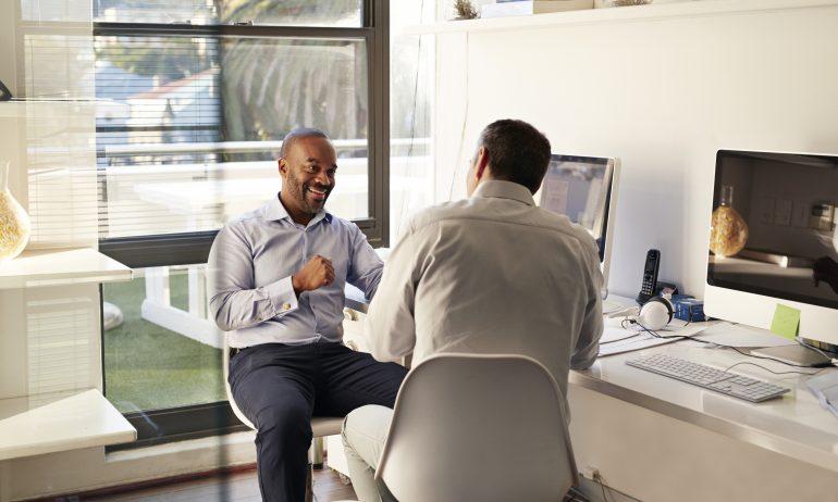 Two businessmen talking at their desks