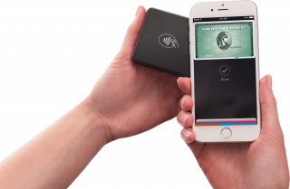 One hand on the right holds up a smartphone to the Payanywhere 3-in-1 reader on the left