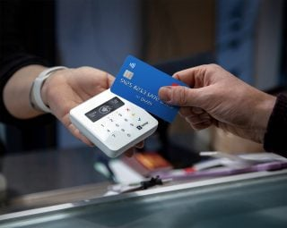 A customer holds a credit card up to the SumUp Plus reader