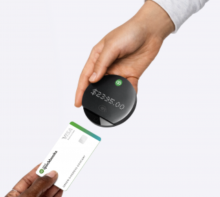 A customer holds a credit card up to the QuickBooks Card Reader